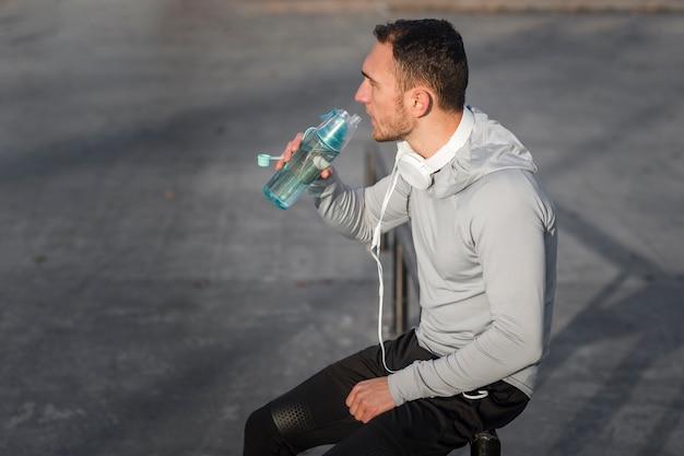 スポーティな若い男は、水を飲む 無料写真
