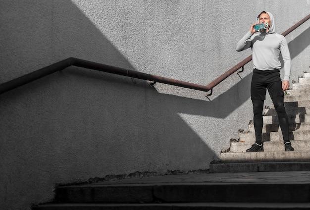 若い男が階段で水を飲むフルショット 無料写真