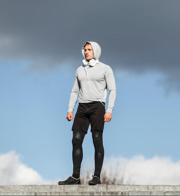 Атлетический молодой человек представляя моду снаружи Бесплатные Фотографии