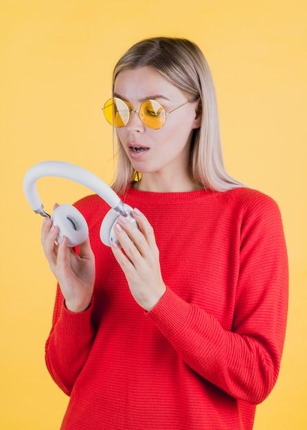 Удивленная женщина, держащая наушники среднего снимка Бесплатные Фотографии