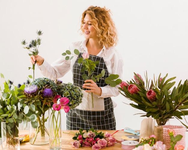 Средний снимок, счастливый флорист, собирающий цветы Бесплатные Фотографии