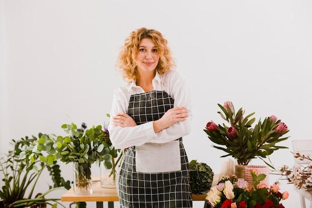 Средний снимок флорист позирует со скрещенными руками Бесплатные Фотографии