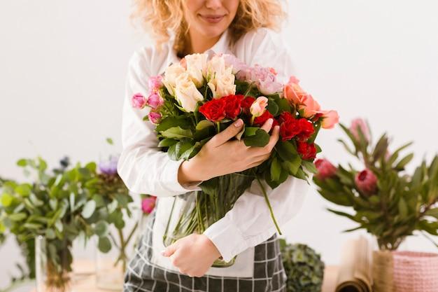 花と瓶を保持しているクローズアップスマイリー花屋 無料写真