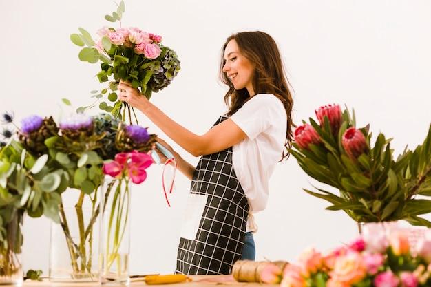 花束を作るミディアムショットスマイリー花屋 無料写真