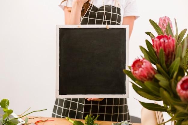 ブラックボードを保持しているクローズアップの花屋 無料写真