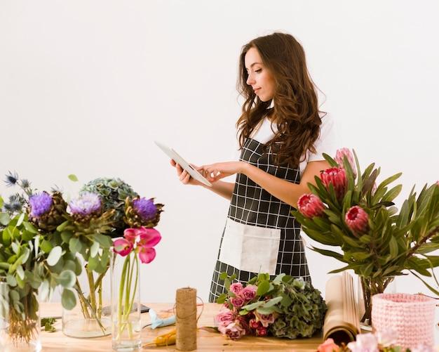 タブレットとエプロンを持つミディアムショットの花屋 無料写真