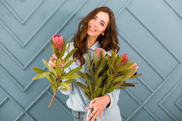 Вид спереди счастливая женщина позирует с цветами Бесплатные Фотографии