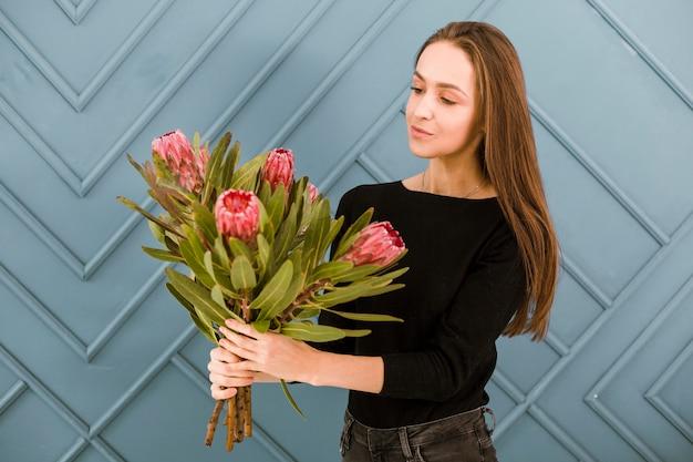ミディアムショットの若い女性が花でポーズ 無料写真
