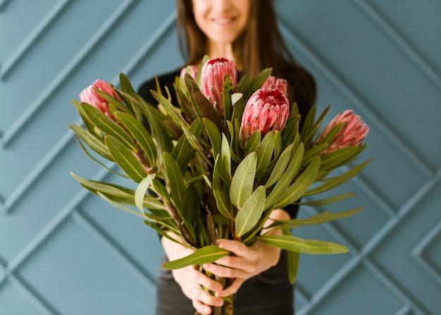 花束を保持しているクローズアップスマイリー若い女性 無料写真