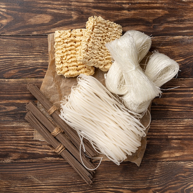 木製の背景に麺の未調理の品揃えを置く 無料写真
