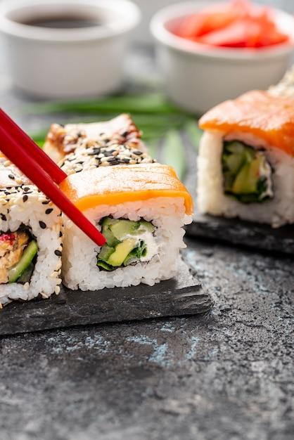 Крупным планом ассорти из суши роллы с палочками для еды на шифер Бесплатные Фотографии