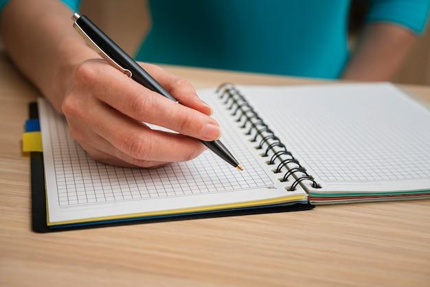 Вскользь женщина пишет в тетради в клетку Бесплатные Фотографии