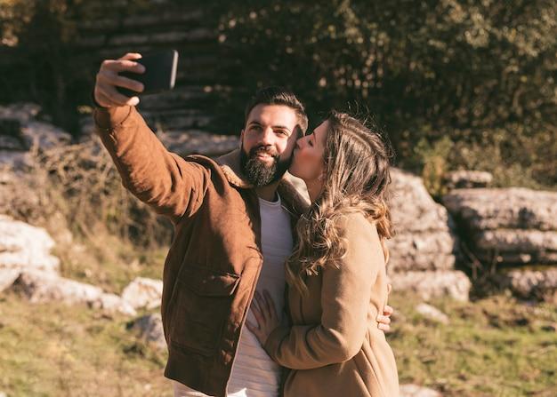 Женщина целует своего парня, пока он делает селфи Бесплатные Фотографии