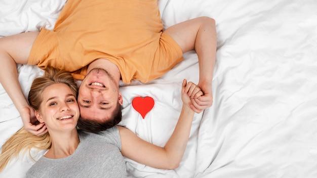 ベッドで手を繋いでいるトップビュー幸せなカップル 無料写真
