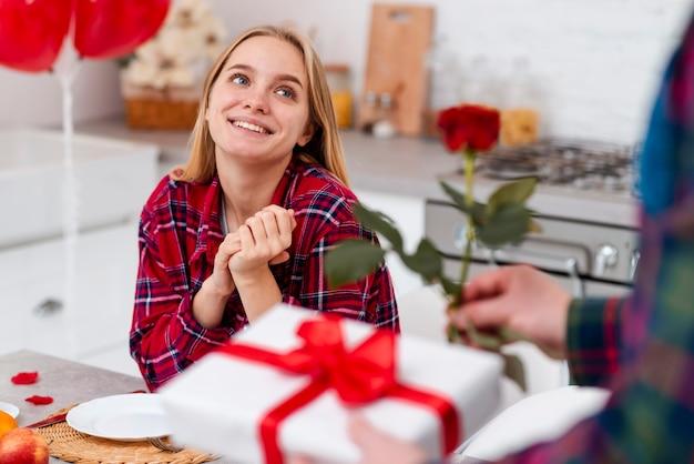 ローズとプレゼントを持つ女性を驚くほどのクローズアップ 無料写真