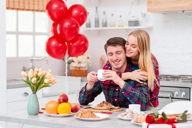 Средний снимок счастливая пара с завтраком на кухне Бесплатные Фотографии