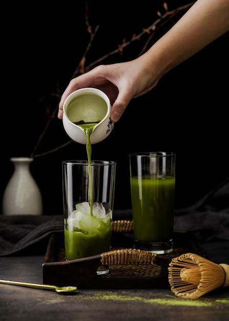 トレイ上のガラスに抹茶を注ぐ手の正面図 無料写真
