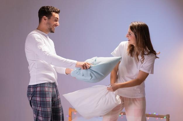 枕の戦いを持っているカップル 無料写真