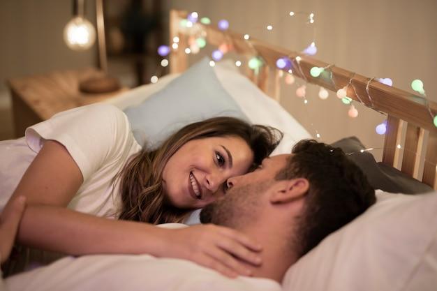 ベッドで寄り添う美しい若いカップル 無料写真