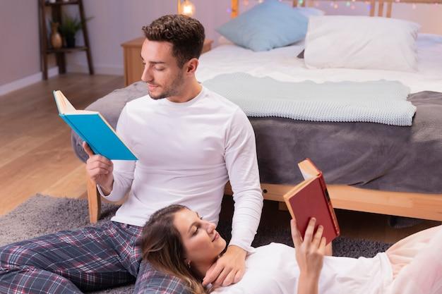 若いカップルは床で本を読んで 無料写真