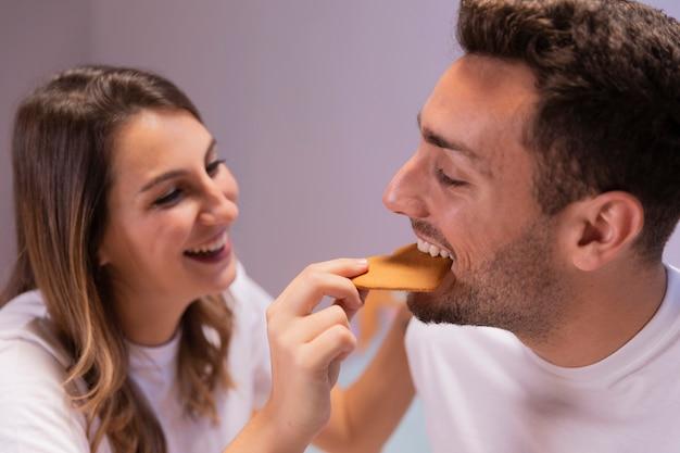 ベッドで朝食を食べる若いカップル 無料写真