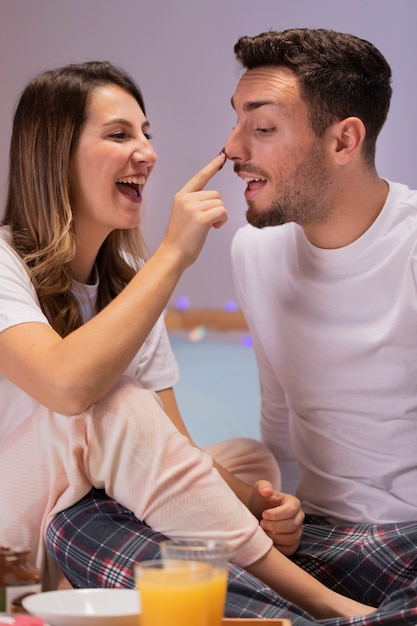 ベッドでお菓子を食べる若いカップル 無料写真