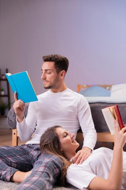 若いカップルがベッドで一緒に読んで 無料写真