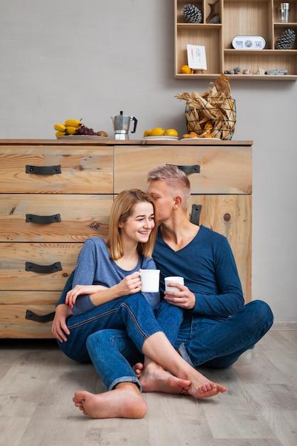コーヒーを飲みながら床に座ってカップル 無料写真