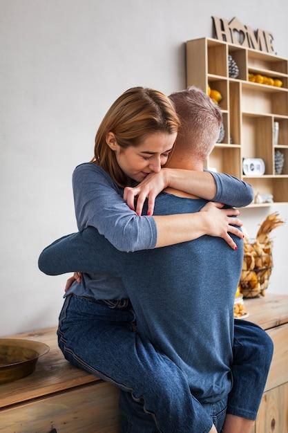 台所で夫を抱き締める女性 無料写真