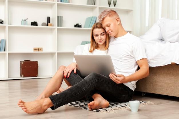 Длинный выстрел мужчина и женщина смотрят фильм на ноутбуке Бесплатные Фотографии