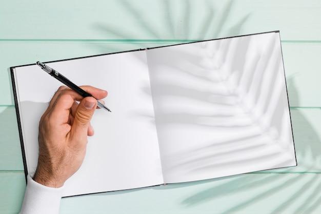 空白のノートブックと葉の影に手書き 無料写真