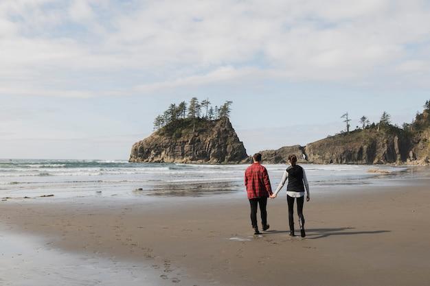 Вернуться мнение пара, держась за руки на берегу Бесплатные Фотографии