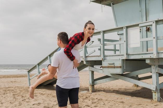 Мужчина несет женщину на пляже Бесплатные Фотографии