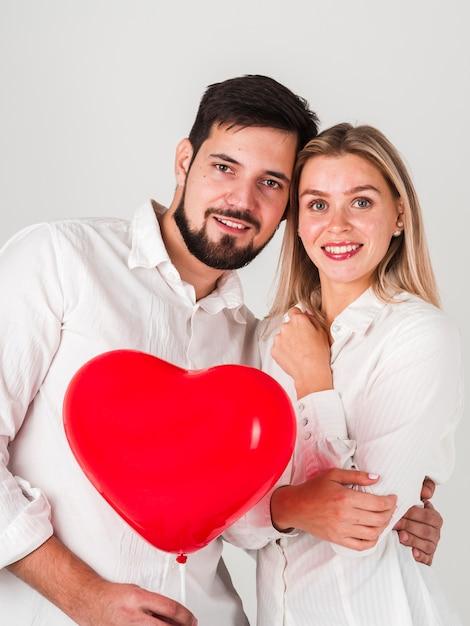 Пара обнялась, держа валентина шар Бесплатные Фотографии
