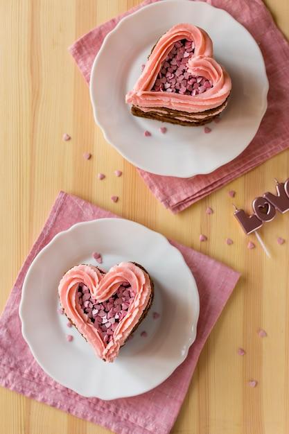 木製の背景にハート型のケーキのスライスのトップビュー 無料写真