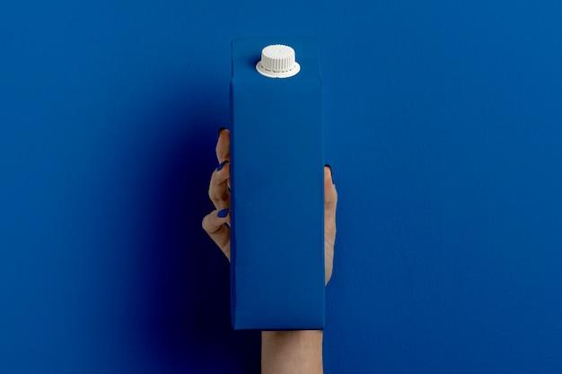 Женская рука держит контейнер для молока на классическом синем Бесплатные Фотографии