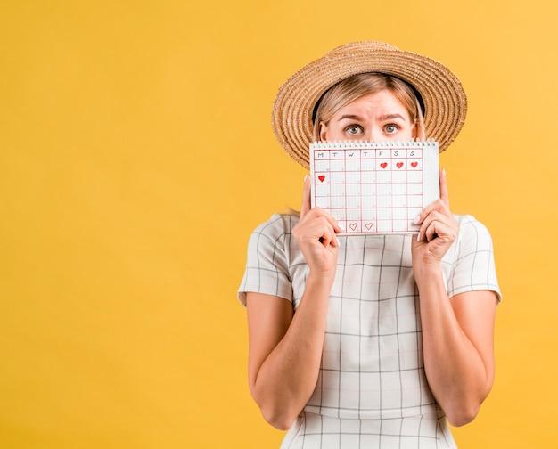 月経カレンダーで彼女の顔を覆っている帽子を持つ若い女性 無料写真