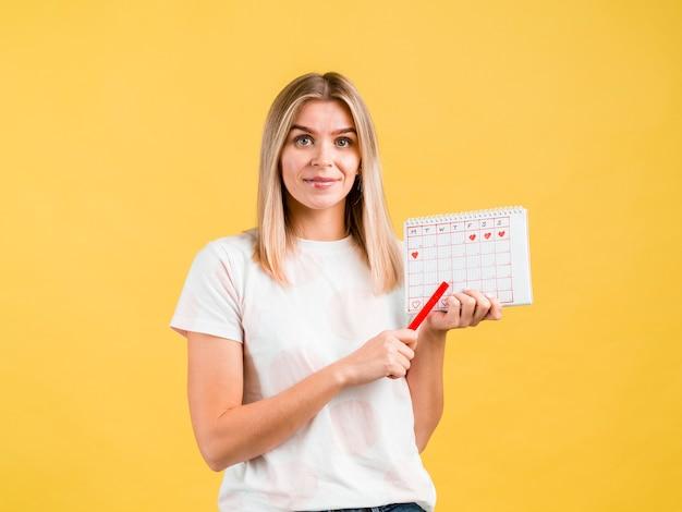 Средний снимок женщины, держащей ручку и календарь Бесплатные Фотографии