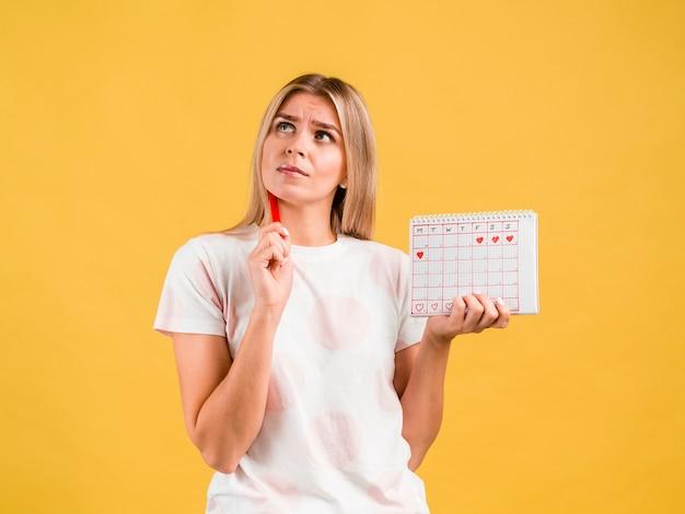 Средний снимок женщины, думающей и держащей календарь периода Бесплатные Фотографии