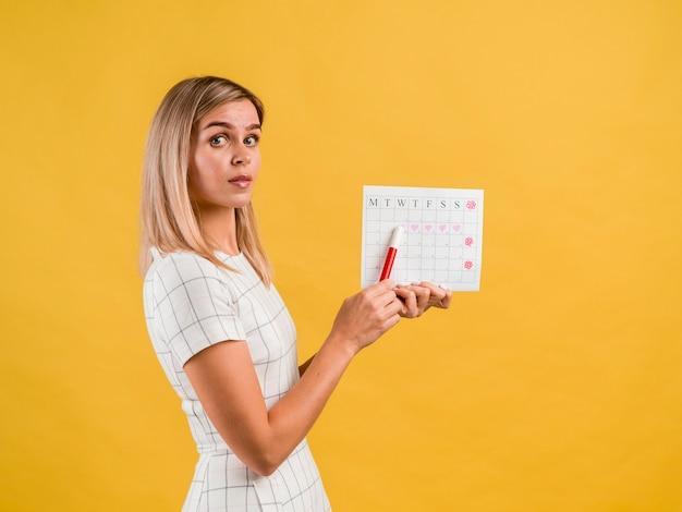 Красивая сбоку молодая женщина с шляпой показать календарь Бесплатные Фотографии