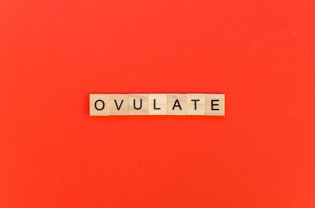 赤の背景にスクラブル文字で単語を排卵します 無料写真