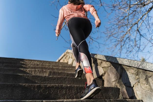 Подходит молодая женщина, поднимаясь по лестнице на открытом воздухе Бесплатные Фотографии