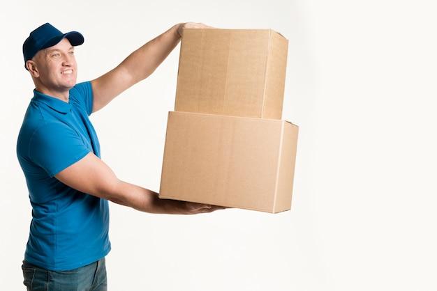 手で段ボール箱を保持している配達人の側面図 無料写真