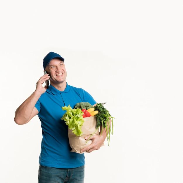 Работник службы доставки смайлик разговаривает по телефону с сумкой Бесплатные Фотографии