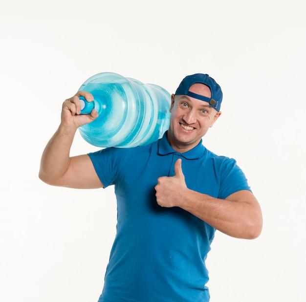 配達人が肩に水のボトルを運んでいる間親指を立てる 無料写真