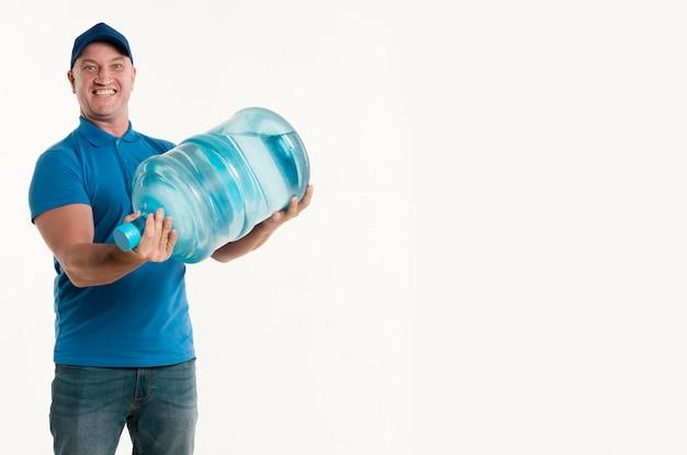 水のボトルを押しながら笑みを浮かべて配達人の正面図 無料写真