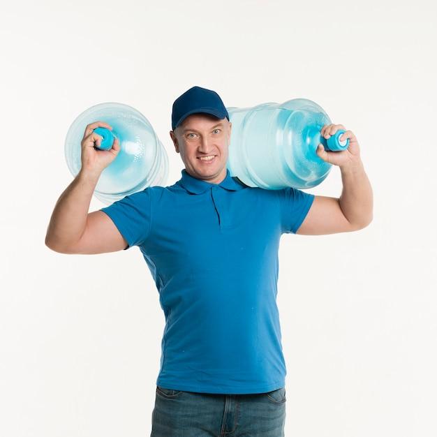 肩に水のボトルを運ぶスマイリー配達人 無料写真