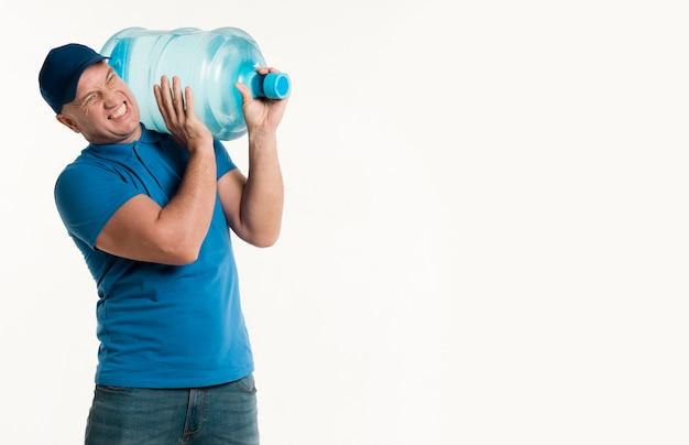 肩に重い水のボトルを運ぶ配達人 無料写真
