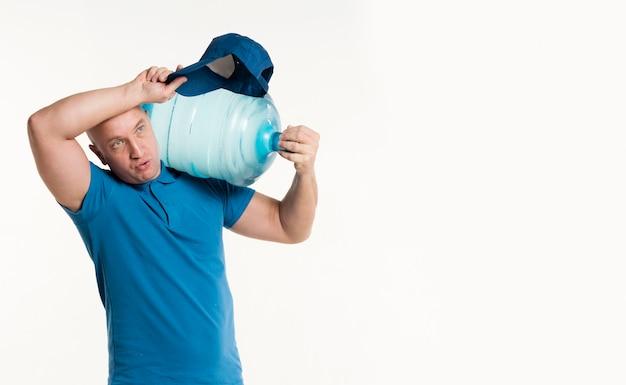 重い水のボトルを保持している配達人 無料写真