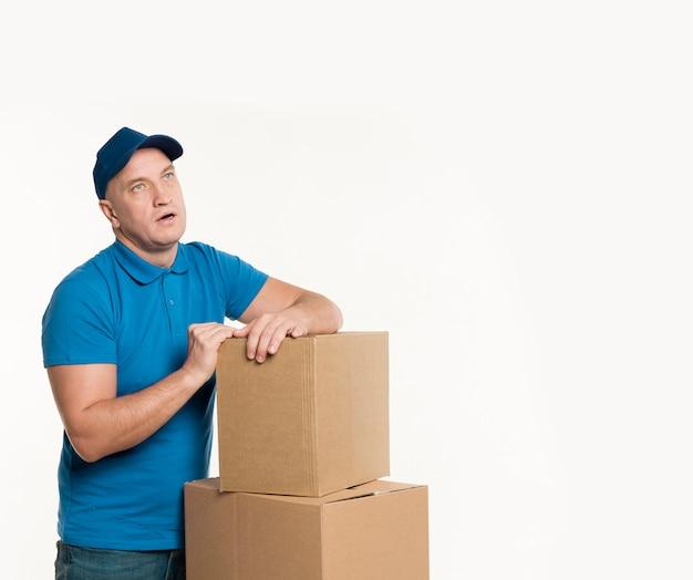 Доставщик с картонными коробками позирует в изнеможении Бесплатные Фотографии